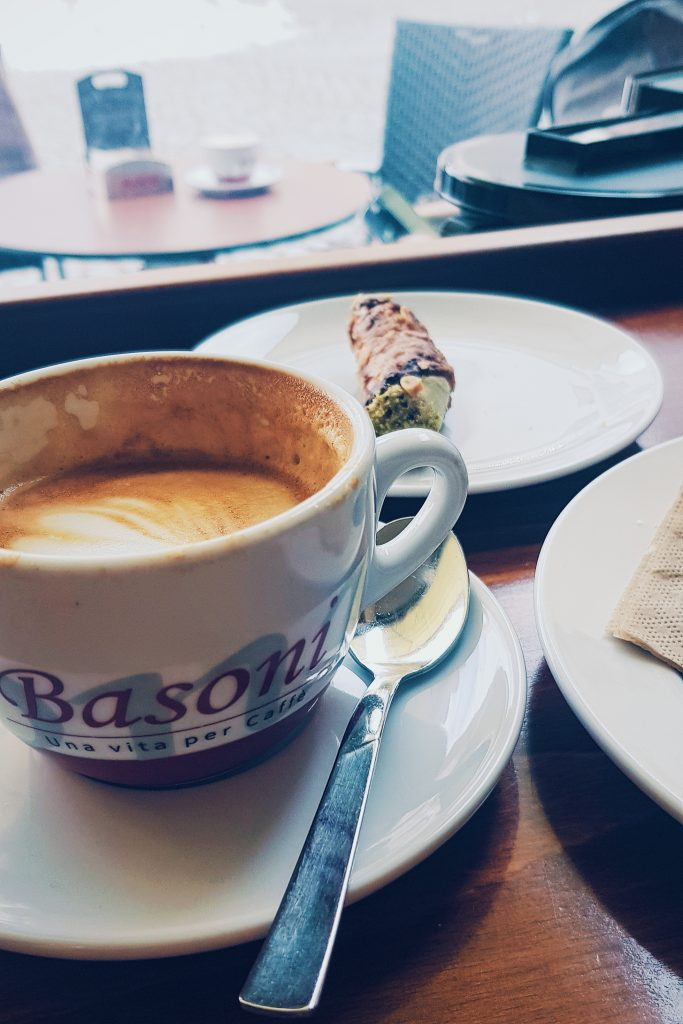 Image of cup of coffee and cannoli Italian snack